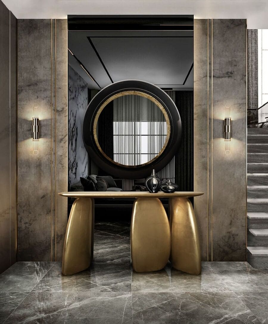 A modern entryway with a luxurious gold sideboard, a black and gold mirror and modern wall lamps.